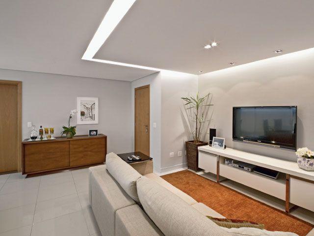 Para ambientar melhor o espaço, a arquiteta Marina Dubal optou por luz focal e quente. No projeto, o rebaixamento em gesso acartonado delimitou a sala de estar, com uma sanca invertida refletindo luz indireta na parede. Esse efeito, além de bonito, deixou o ambiente mais aconchegante.
