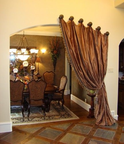 Portier Drapes create a dramatic entrance to an elegant room. - you could do something like this (only more rustic) between your den and dining room