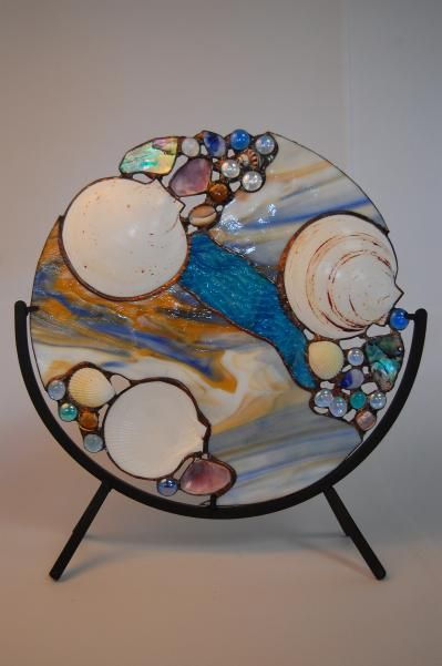 Hrmmmm… I wonder if you could bake seashells, maybe some glass agates and then the plastic beads that melt, into an aluminum pie plate like the wind chimes