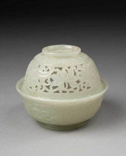 Brûle-parfum en néphrite blanche légèrement céladonné.  à décor sculpté en léger relief de lotus et rinceaux feuillagés de deux frises de pétales de lotus et lingzhi. Le couvercle est ajouré du même décor. Au revers de la base et sur le couvercle la marque de Qianlong. Hauteur : 10 cm, Diamètre : 12,7 cm - Estimation : 20 000 / 30 000 € Pas d'adjudication