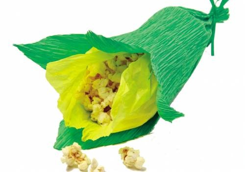 Você vai precisar de papel crepom nas cores verde e amarelo. Primeiramente, corte retângulos (em torno de 20 cm x 30 cm) de cada uma das cores. Enrole o papel amarelo no sentido horizontal e prenda um dos lados com grampeador ou durex. Faça o mesmo com o retângulo verde, envolvendo a estrutura amarela.    Para fechar, amarre uma das pontas com uma tirinha reforçada de papel. Por fim, use uma tesoura e corte a ponta livre do papel verde, simulando uma casca de milho sendo aberta.