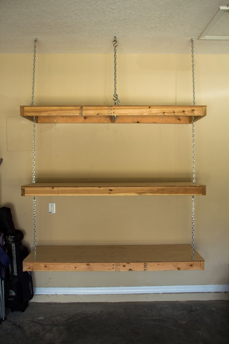Hanging garage shelves. Eye bolt in ceiling goes through ceiling joist for ultimate strength. Chains support front weight. Rear weight supported via lag bolts going into wall studs.
