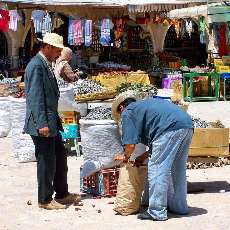 A man is buying some fish  and chili pepper for lunch at a market stall in Djerba Tunisia.