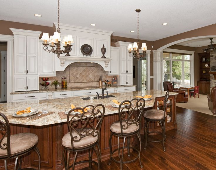 Large, open kitchen features immense island done in natural wood tones, with built-in glass cabinetry, dining area, and full sink on marble countertop.
