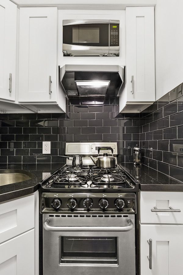 Valentino installed a gleaming subway tile backsplash in black glass, and crisp white paint brightens up the new space. The studio's owner went for stainless appliances in lieu of the older white originals, and she particularly wanted a vented hood for the oven range. Valentino saw to it that these accessories were incorporated in the design.