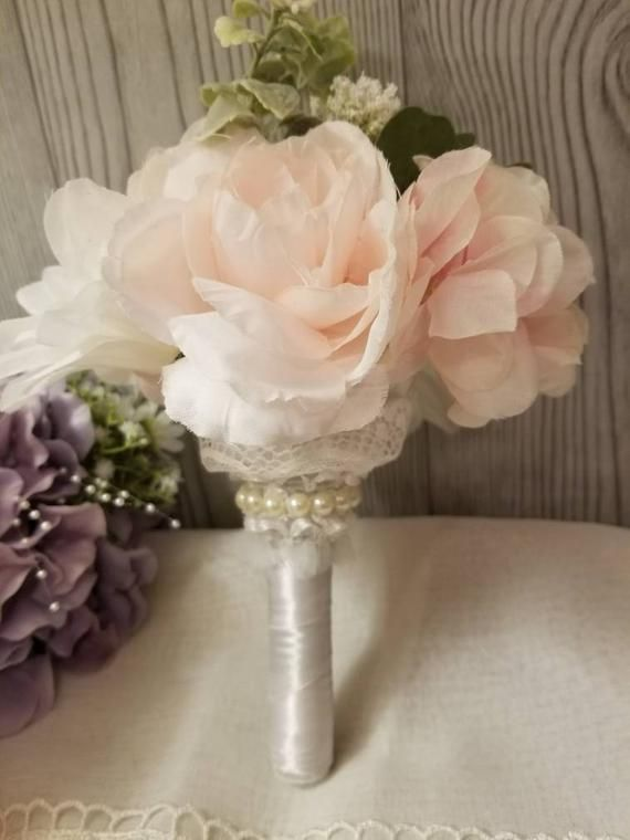 This Is A Small Bouquet Holder That Is Wrapped In White Satin