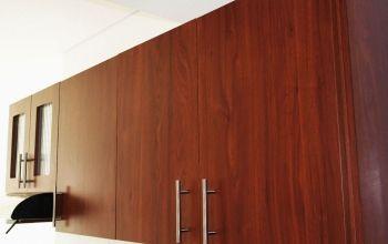 Mueble alto de cocina integral, enchapado en formica color cedro y manijas en acero inoxidable.