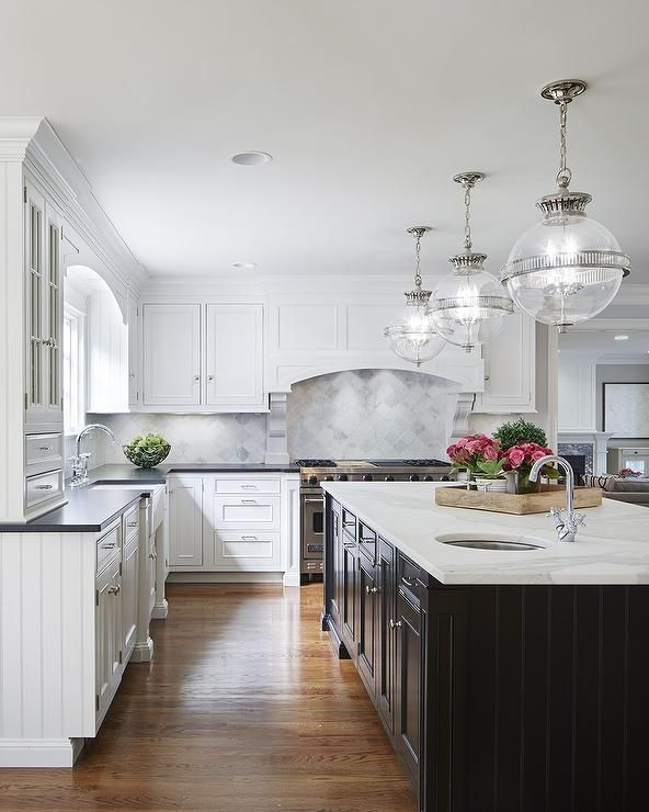 White and black kitchen features white cabinets painted Benjamin Moore White  Dove paired with .