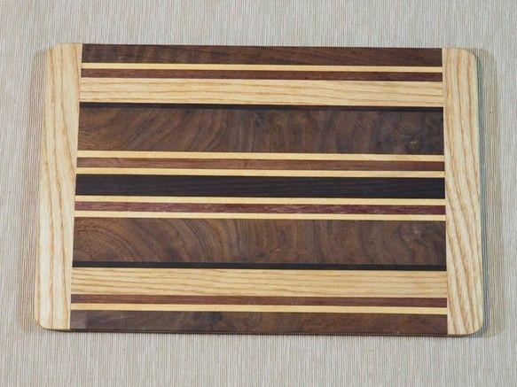 寄木細工のカッティングボードです!!パドウク、ウォールナット、ヨーロピアンビーチ、ホワイトアッシュ、ウェンジの5種類の天然木を使用しています。バケットやチーズ、果物などをのせてプレートとしてもご使用いただけます。防水加工後、オリーブオイルを塗布して仕上げています。※天然木を使用した商品の為、写真と実物との木目が違います。ご理解の上お買い求め頂きます様宜しくお願い致します。※ご注文を頂いてから製作を致しますので、通常発送までに30日前後お時間を頂いております。サイズ:約37㎝×24㎝×1.5㎝