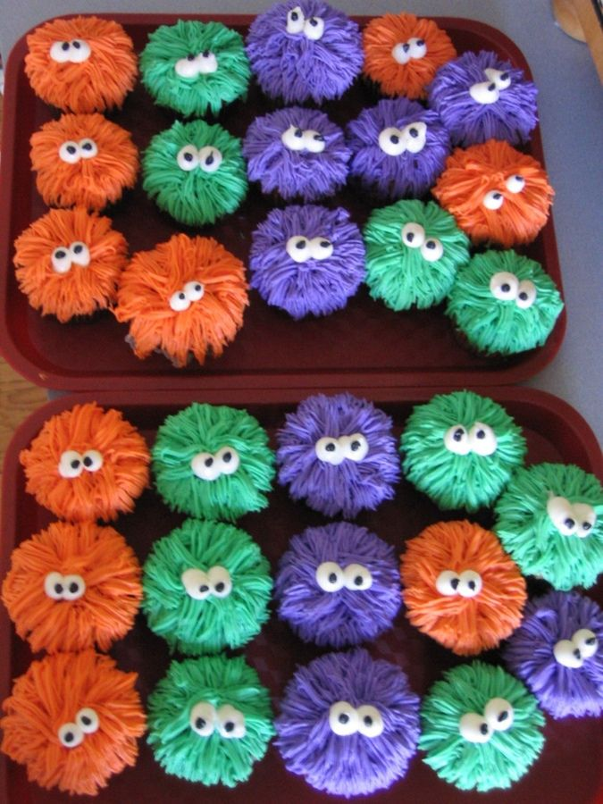 "Monster Cupcakes. She used the ""grass"" tip. Just start from the outside of the cupcake and work inward. Then add the eyes."
