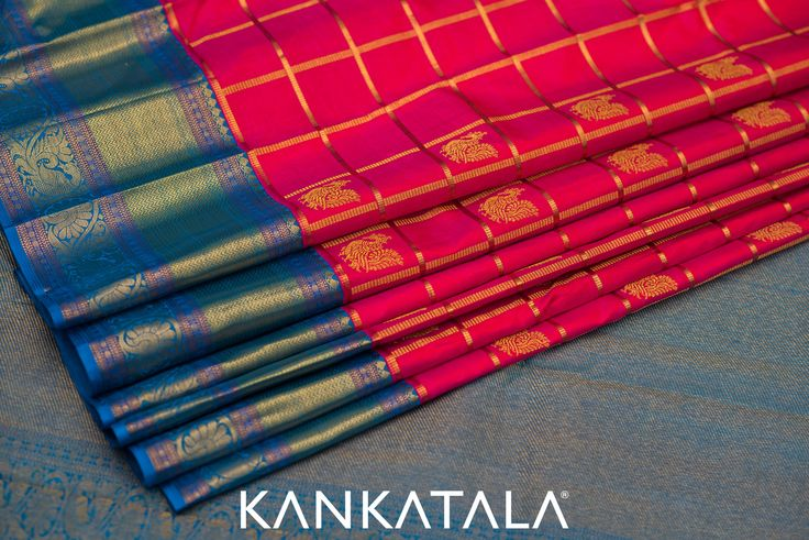 Checkmate! When a Kanchipuram saree this beautiful is before you, there is only one option - surrender! With a stunning pink checked body with zari checks and buttas, and an alluring big blue border with attractive peacock motifs - surrendering is a triumph!! #KanchipuramSaree #SilkSaree #Drapes #BridalSaree #Bridetobe #kankatala