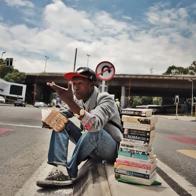 Instead of begging, homeless man reviews books on the street and sells them (but not to kids). Read more - http://twentytwowords.com/instead-of-begging-homeless-man-reviews-books-on-the-street-and-sells-them-but-not-to-kids/ #bethechangeReading, Begging, Sell, South Africa, Man Sitting, People Pass, Young Man, Empire Roads, Book Reviews