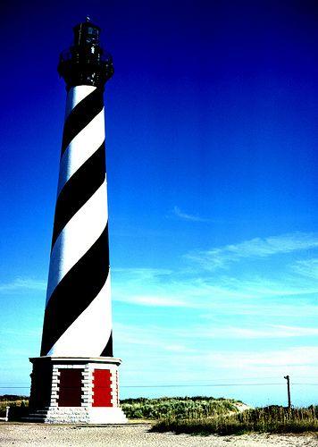 """Farol do Cabo Hatteras, Carolina do Norte, USA. Este farol icônico é o mais alto nos Estados Unidos. Ele protege uma área da costa da Carolina do Norte conhecida como o """"Cemitério do Atlântico"""", onde o deslocamento de bancos de areia afundou muitos barcos, incluindo o navio da Guerra Civil, o USS Monitor. Esta torre de 64 m de altura pode ser vista até 50 milhas de distância.  http://www.plumdeluxe.com/spectacular-lighthouses-from-around-the-world"""