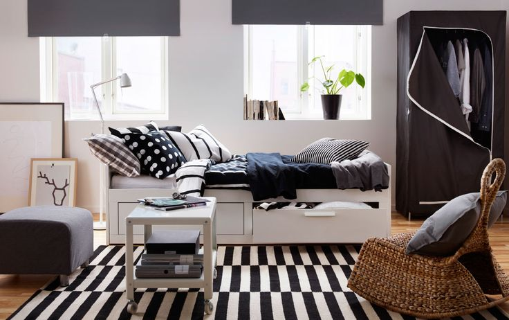 Letto bianco con cassetti e biancheria da letto in bianco, nero e grigio.