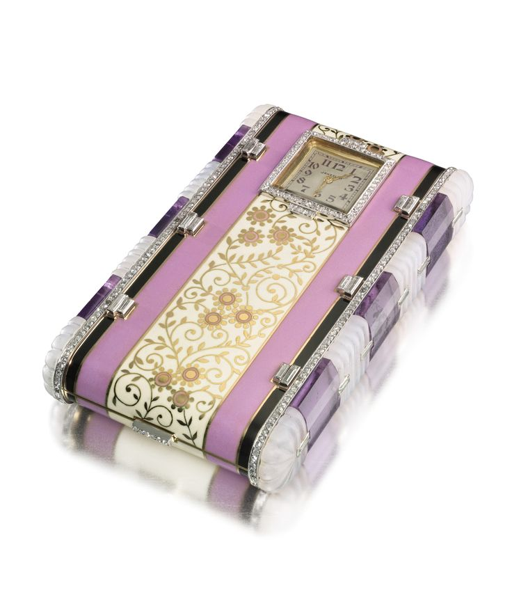 Vanity case with black and pink enamel stripes, the central stripe of cream enamel with floral design, set with a watch at one end outlined in round diamonds, the long edges of the case similarly set with round diamonds and accented with baguette diamonds, the sides set with rock crystal and amethyst segments linked with baguette diamonds, the button clasp set with round diamonds; interior with fitted mirror, powder compartment, and lipstick holder
