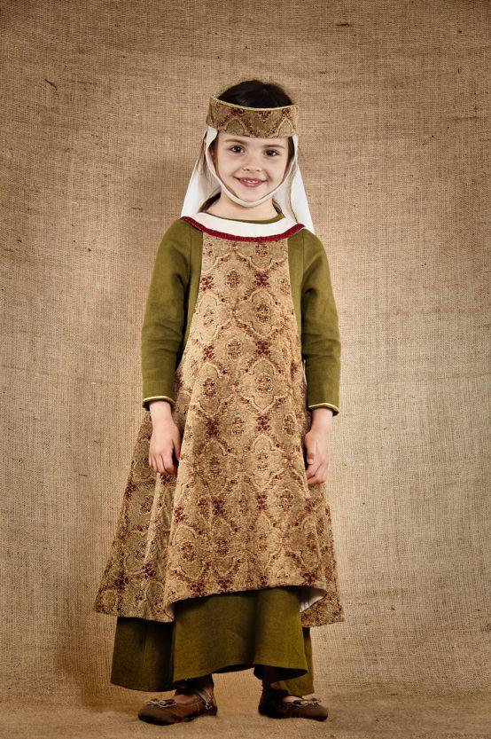 Costume médiéval de noble Dame inspiré de la fin du 13ème siècle composé de 3 pièces : une robe de dessous en lin lavé de couleur verte avec laçage dans le dos, une sur-robe en velours lisse et soyeux et une coiffe assortie réglable, agrémentée d'une sous-gorge et d'un voile en lin écru. Ce modèle est disponible du 4 au 12ans à partir de 189€. Tous les costumes proposés par 7 et une Lieues sont de fabrication artisanale et de très grande qualité.