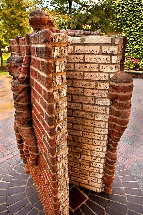 Brick Book Statue - Stone children climb on a giant brick book statue, one of the many public art offerings in Charlotte, North Carolina. The statue is located on The Green Uptown, a passive park .. includes fountains, landscaped walkways, motion-activitated stone walls, chess boards built into stone tables and riddles on the ground. Photo: PatrickSchneiderPhoto.com