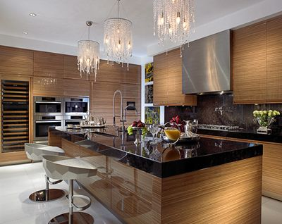A clean, contemporary, polished kitchen with high gloss zebra wood cabinetry, antique brown granite countertops, and Miele appliances. Love the silver-lacquered Fendi barstools, and crystal dangle light fixtures. Interior by Steven La Fonte Design.