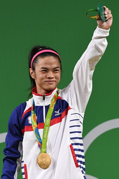 Tawain's Hsu ShuChing poses with her gold medal on the podium after the women's 53kg weightlifting event at the Rio 2016 Olympic games in…