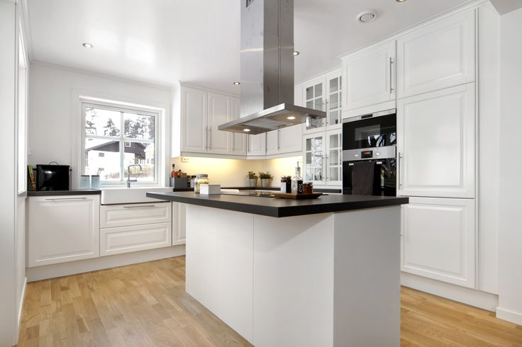 Nydelig kjøkken med komfyren plassert på øya i midten av rommet