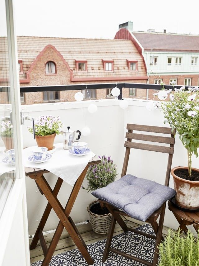 Outdoor balcony with table, chair, cushions, and lights