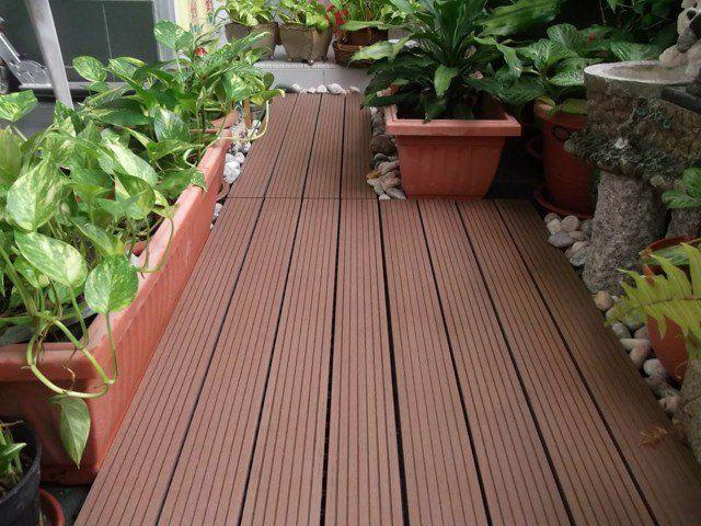 revêtement de sol en bois composite et des plantes vertes sur le balcon
