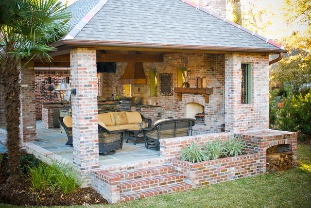 outdoor kitchen/living space (side view).  Brick, slate floor, bahama shutters, lantern, planter...