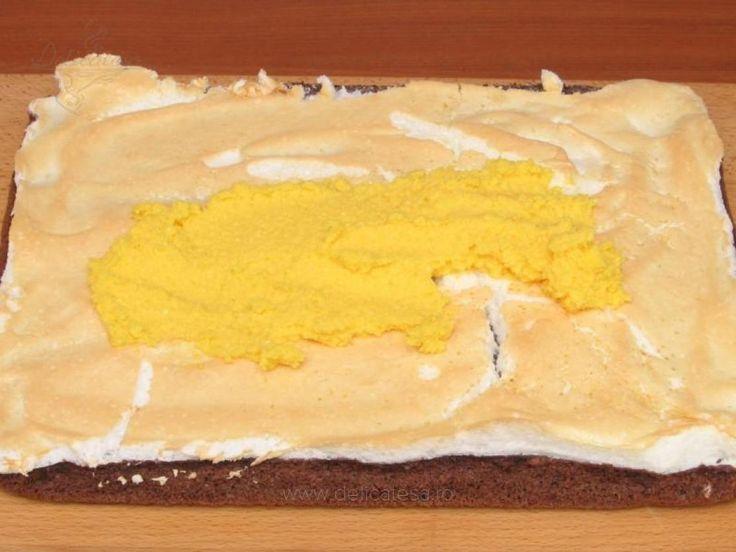 Peste blatul scos din cuptor se adaugă bezeaua, se întinde uniform pe toată suprafaţa şi se coace la 150 grade timp de 20 de minute, până se întăreşte bezeaua. Se scoate din cuptor, se lasă să se răcească, după care se întinde crema peste bezea. Deasupra se pune ciocolată rasă.