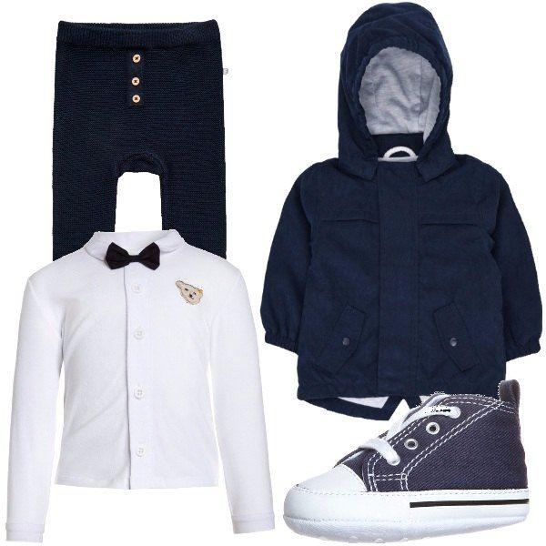Giacca da mezza stagione colore dress blues con cappuccio, maglia a manica lunga bianca con papillon, pantaloni lunghi con bottoni e sneakers con lacci.