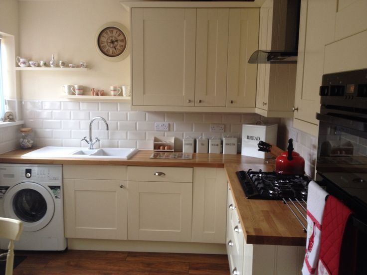 Kitchen fitted doors vanilla with cream subway tiles oak worktop