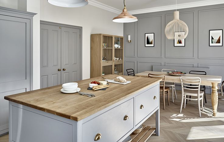 Kitchen island with oak top and brass cup handles and copper pendant lighting. Wall panels in matching grey/blue finish. Contemporary dining table with mismatched chairs.