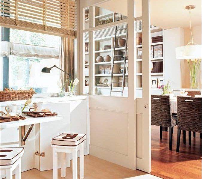 Cocina con puerta corredera acristalada hacia el comedor, persiana veneciana, mesa abatible y taburetes.