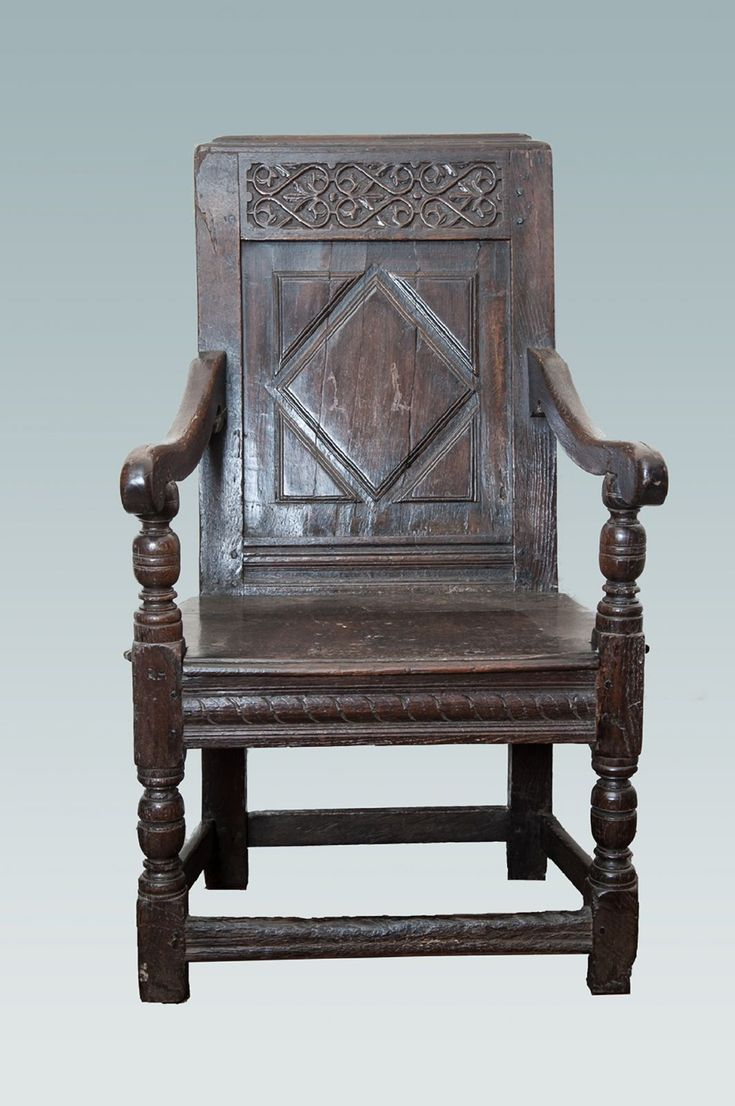 Early 17th century joined oak armchair, with a large single back panel with a deep cut moulding with a diamond and spandrels, the upper rail carved with three double s-scrolls and the seat rails with a repeated S carved decoration.  Possibly Welsh Marches.