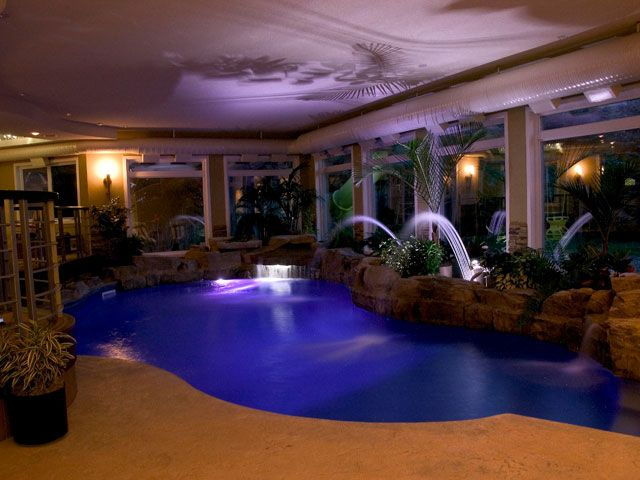 elegant indoor swimming pools with purple effect water design and fountain http