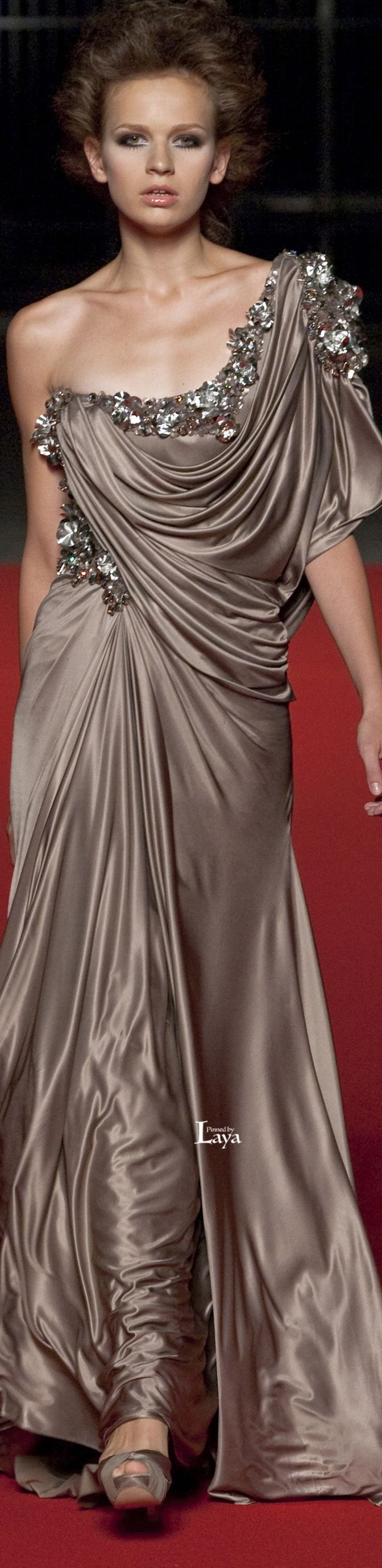 LAYA ABED MAHFOUZ Couture - alluring and seductive, Grecian style gown in a deep taupe with embellishment across the bodice and over the shoulder. The draping of the luxurious fabric is done with finesse and the otherwise plain gown needs nothing else. The supple fabric does all the work.