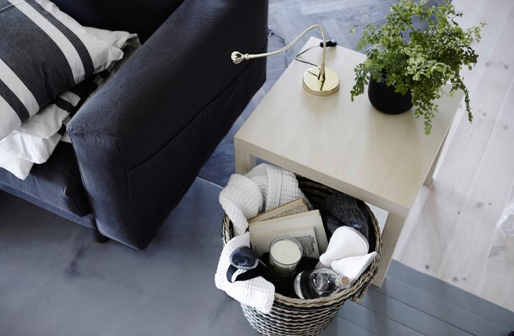 A large basket filled with slippers, a blanket, books, and a candle, placed under a side table, next to a sofa.