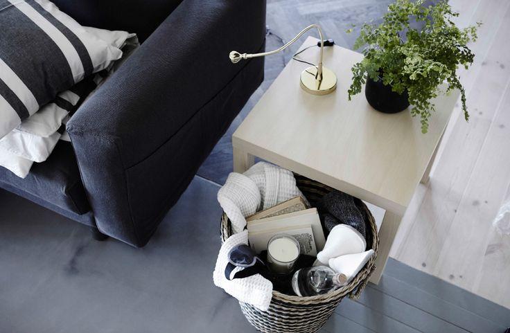 En stor kurv fylt med tøfler, et pledd, bøker og et stearinlys, plassert under et bord ved siden av sofaen.