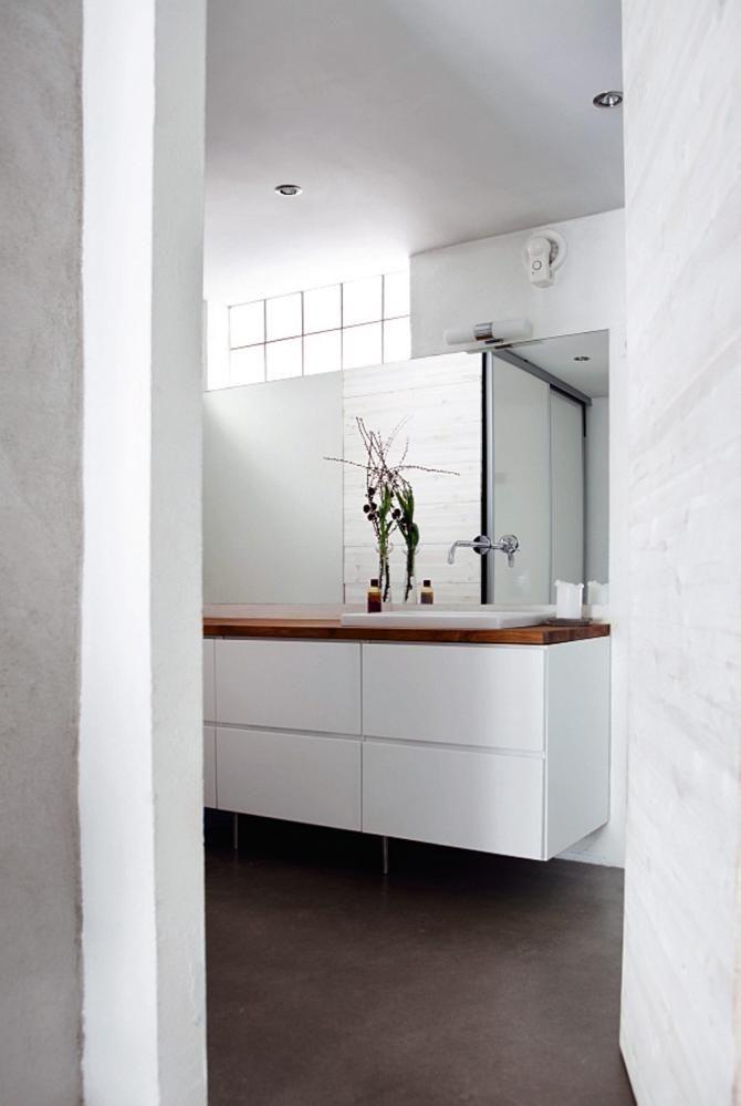 Hvitt, moderne bad med baderomsinnredning fra Kvik, armaturet er fra Hans Grohe. Speilet er laget av Lysaker Glass etter mål.