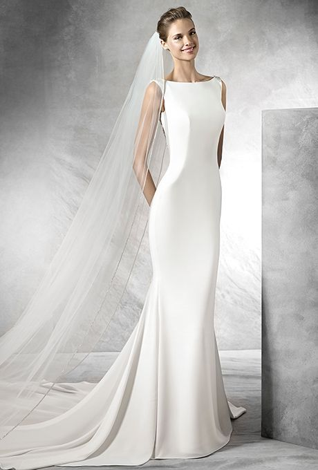 Brides: Pronovias. Simple crepe mermaid dress with gemstone embroidery appliqués. Lace bodice with bateau neckline and plunging V-neck back decorated with gemstone embroidery.