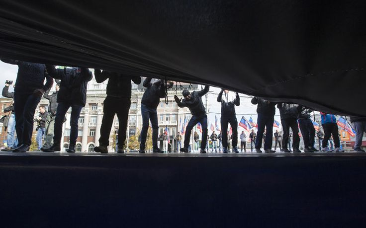 Men hold a giant flag of the self-proclaimed Donetsk People's Republic during a rally on Lenin Square in the centre of a rally was organised to mark the Day of Flag of the Donetsk People's Republic.