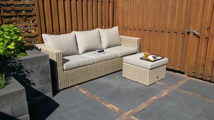 Loungebank van vlechtwerk in de kleur beige met zachte kussens en hocker