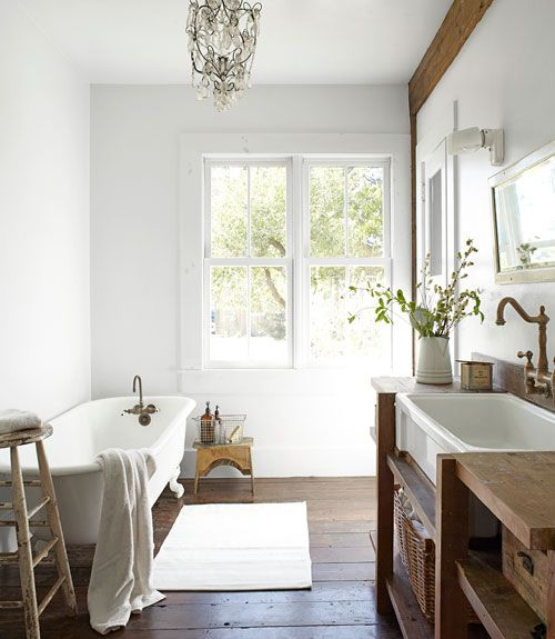 Bright Bathroom  Handmade by Albright, the bathroom's fir sink support holds an Olympia basin. Pattee scored the chandelier, hanging above the vintage claw-foot tub, on eBay.