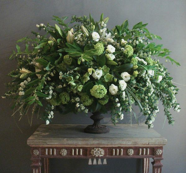 A late spring garden arrangement of spirea, viburnum, lilies, variegated liriope, lisianthus, green hellebores, and Solomon's Seal in a 19th-century French cast-iron urn