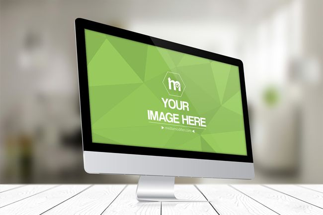 A free online mockup of an iMac computer on a white wood surface and blurred office background. Create a professional display of your website or any other image. Upload your image, crop and create a preview in seconds. A perspective 3D iMac computer monitor online mockup generator.