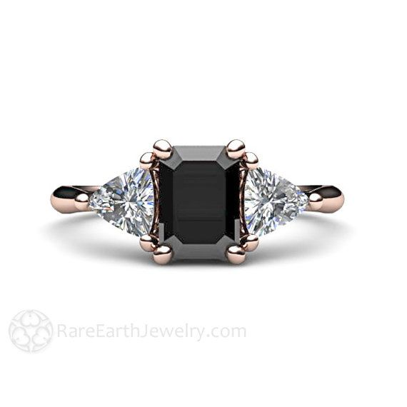 An absolutely stunning vintage inspired black diamond three stone ring in your choice of 14K or 18K White, Yellow or Rose Gold. The black diamond is approximately 1.15 carats and is surrounded by two sparkling diamond trillions, .50ct total weight.  Prefer a different grade of diamond? Id be happy to help you select the perfect diamond for you.  This ring would make a beautiful engagement ring. The matching wedding band is also available. Ask for a quote on the set.  Official Website…