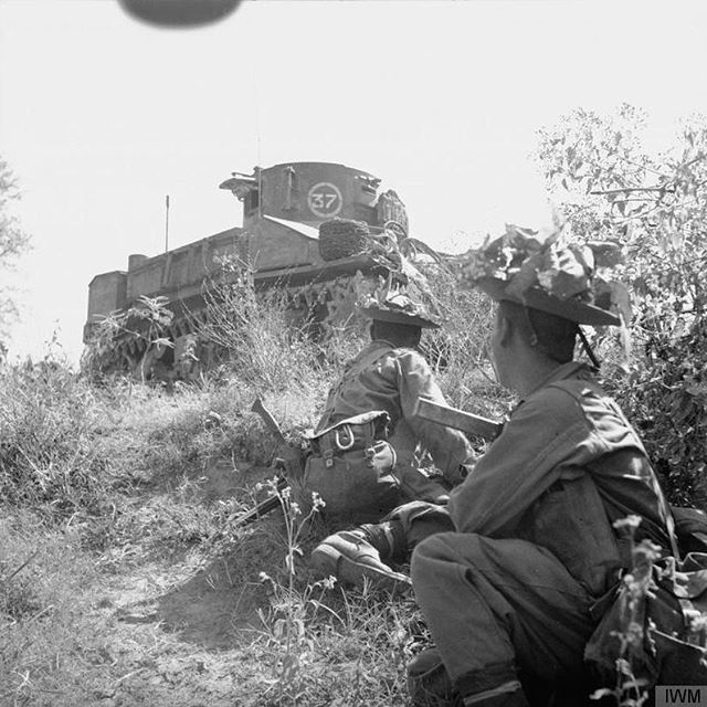 Two Gurkha soldiers apart of the British 6th Queen Elizabeth's Own Gurkha Rifles sit on the bottom of a little hill in the city of Singu, Burma. They are looking up at a M3 Stuart tank. February 1945.