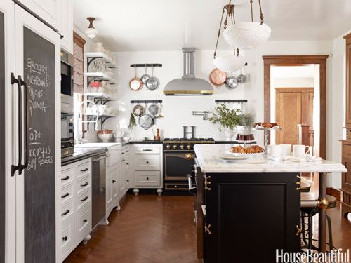 Raised kitchen cabinets make for easy cleaning. A kitchen island offers ample seating, and pots are easily accessible since they're hung on either side of the stove. Design: Nicole Hough.