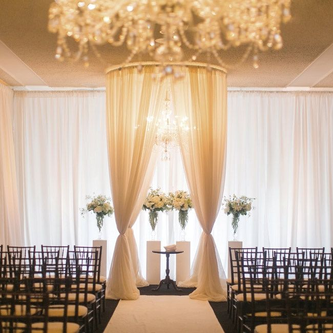 gorgeous and simple elegance wedding ceremony- black chairs, elegant white draping, and chandeliers and flowers