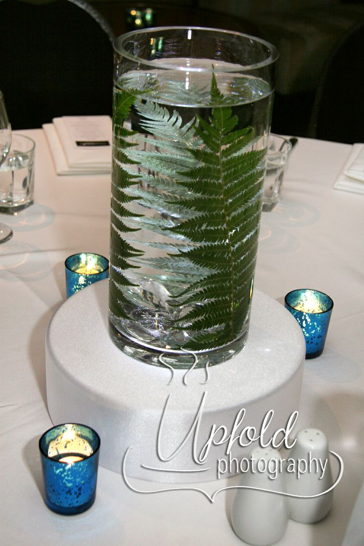 Simple wedding table using a Silver Fern frond inside a glass vase.  Image by Upfold Photography.  ~ Silver Fern table centrepiece ~ Elegant Wedding table centre ~ use of votive candles ~