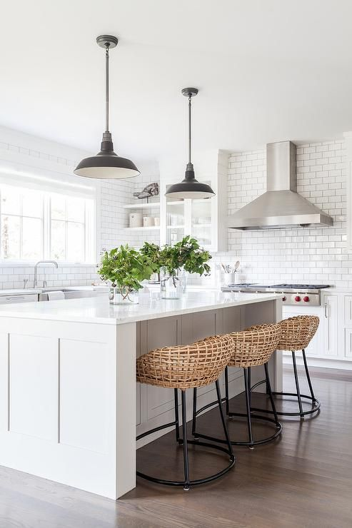 Three woven bar stools sit in front of a white wainscot island complemented with a white quartz countertop illuminated by two black vintage barn pendants.